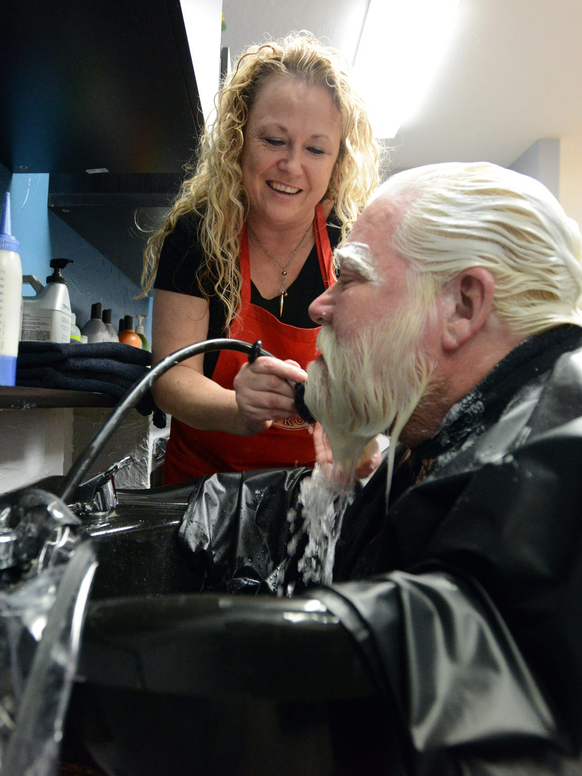 Stacia Cohagan rinses bleach from Tim Etienne's beard