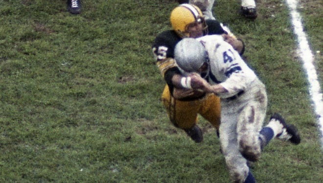 Green Bay Packers linebacker Tom Bettis (65) tackles Detroit Lions receiver Terry Barr (41) at new City Stadium on Oct. 2, 1960. The Packers won 28-9.