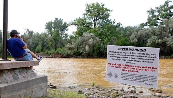 A warning sign from the city is displayed in front of the Animas River as orange sludge from a mine spill upstream flows past Berg Park in Farmington, N.M., Saturday.