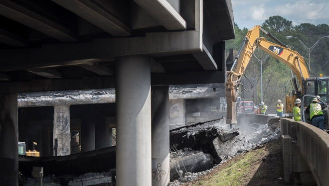 Crews clean up the scene of the Interstate 85 bridge collapse in Atlanta on March 31, 2017. The section of overpass collapsed the day before in a massive fire.