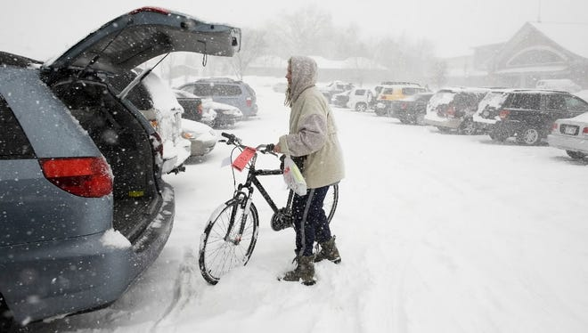 A woman wheels a new bike to her vehicle in the middle of a spring snowstorm March 21, 2008, during the annual bike expo sponsored by Wheel and Sprocket at State Fair Park in West Allis. Total snowfall for West Allis from that storm was 18.5 inches.