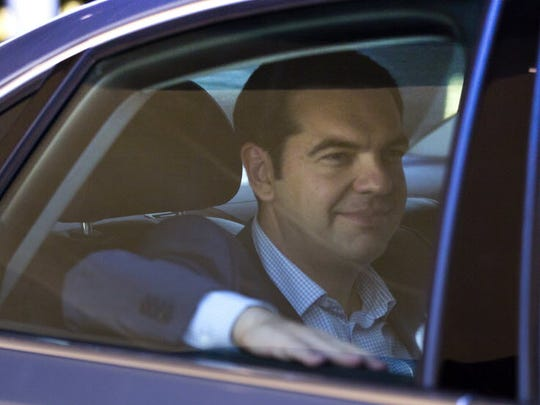 Greek Prime Minister Alexis Tsipris leaves in his car