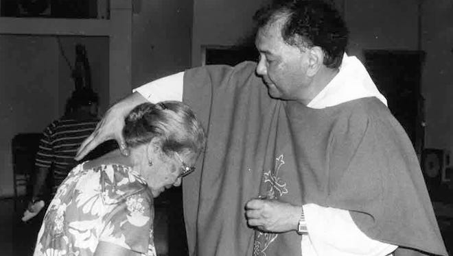 Father Daniel Cristobal anoints a Sinajana parishioner with the oil of St. Jude in this file photo from October 1987.