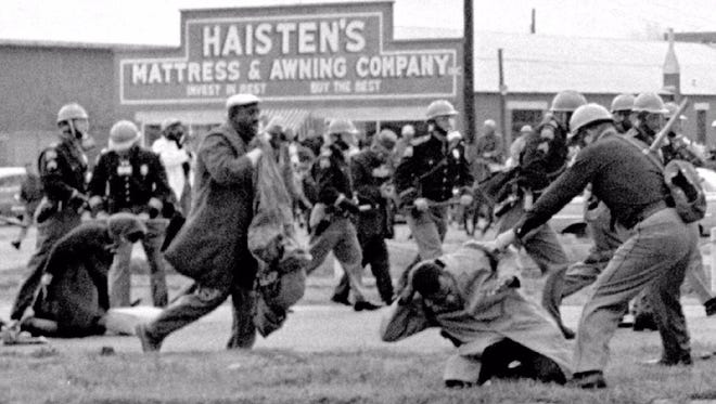Alabama state troopers swing billy clubs to break up a civil rights voting march in Selma, Ala., on March 7, 1965. John Lewis (front right) is held to the ground.