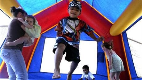 FILE - In this Sept. 11, 2005 file photo, children play in a bounce house in Vidor, Texas.