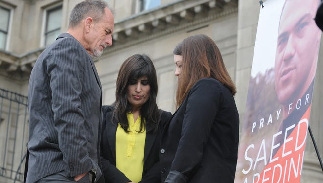 Pastor Bob Caldwell of Calvary Chapel of Boise, left, prays Sept. 26, 2013, on the Idaho capitol steps with Naghmeh Abedini, center, and Tiffany Barrans of the American Center for Law and Justice. Thousands of people gathered in vigils across the USA to pray for the safe return of Pastor Saeed Abedini, incarcerated in Iran one year ago for preaching Christianity, supporters say.