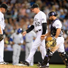 Aug 19, 2014; Denver, CO, USA; Colorado Rockies pitching coach Jim Wright (52) walks over to relief pitcher Rex Brothers (49) along with catcher Michael McKenry (8) after he loads the bases in the eighth inning against the Kansas City Royals at Coors Field. Mandatory Credit: Ron Chenoy-USA TODAY Sports