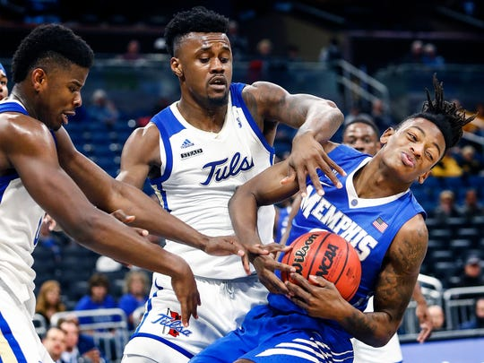 Memphis forward Kyvon Davenport (right) grabs a loose ball against Tulsa the defense during second half action of their AAC second round tournament game in Orlando, Fl., Friday, March 9, 2018.