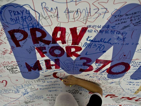 A Malaysia Airlines employee writes a message expressing