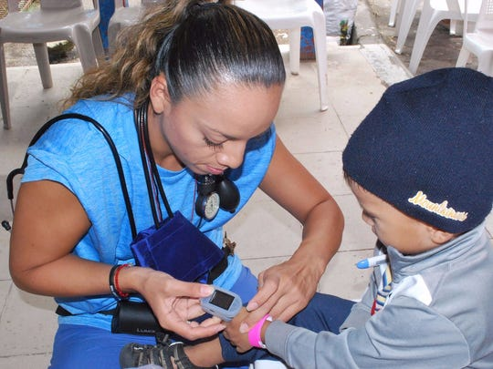 Jennifer Padilla, an Emergency Medical Technician and Certified Phlebotomy Technician at Eisenhower Medical Center's Emergency Department in Rancho Mirage, checks a little boy's temperature during the IMAHelps medical mission to Matagalpa, Nicaragua.