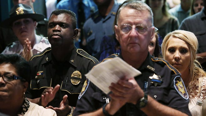 Police officers and other mourners gather during a memorial service honoring two slain Hattiesburg, Miss., police officers.