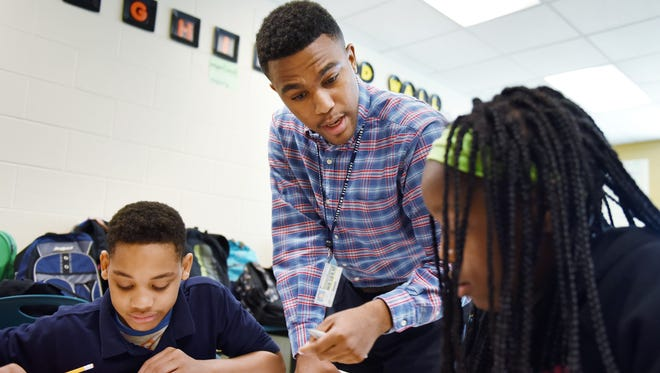Student teacher Edward Williams helps sixth-graders Keelyn Green, left, and Ashanti Shelton with an exercise in teacher Etoria Hill's math class on Friday at Blackburn Middle School in Jackson. Williams will graduate from Jackson State University in May and be ready for a classroom of his own in the fall.