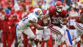 Oklahoma Sooners running back Samaje Perine (32) runs for a touchdown past Kansas Jayhawks linebacker Courtney Arnick (28) during the first half at Gaylord Family - Oklahoma Memorial Stadium.