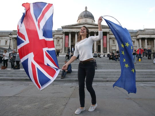 A Pro-European Union protester holds Union and European flags in Trafalgar Square during a rally in central London on Sept. 13, 2017, to warn about the terms of Brexit, by EU nationals in Britain and U.K. nationals in Europe.