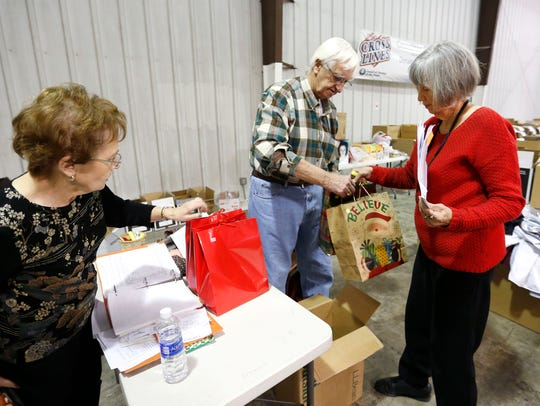 Sheryl Wachter (left) and Clyde and Judy Paul sort