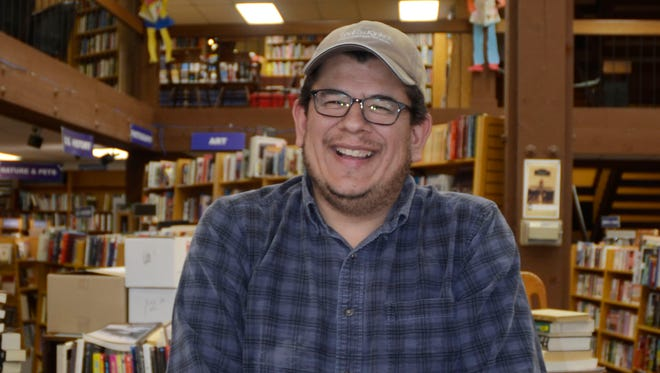 "Adam Gallardo, a local novelist, prices books at The Book Bin in downtown Salem on Tuesday<137>, May 6, 2014<137>. His first prose novel, ""Zomburbia,"" will be published Aug. 26."