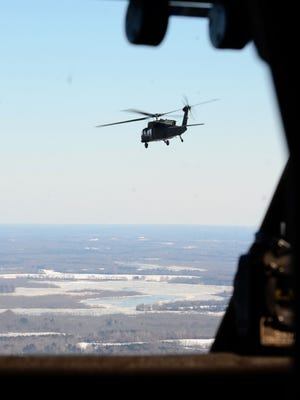 A Virginia National Guard  UH-60 Black Hawkhelicopter flies supplies to Tangier Island.