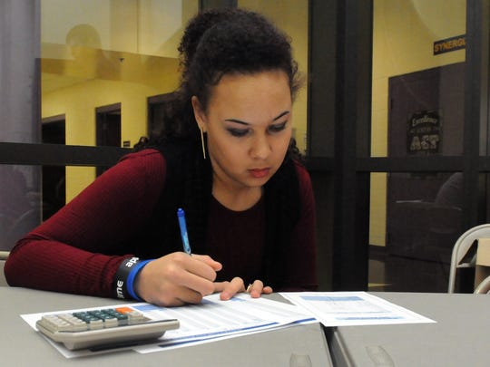 Lauren Henry, bookkeeper, checks the cash count after