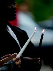 Attendees hold candles during a candlelight vigil held for Mekhi Luster, the 18-year-old victim of shooting in Southwest Knox County, at Sam Hill Park in Knoxville, Tennessee on Tuesday, April 24, 2018.