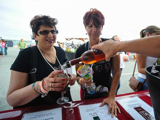Lyn Oyer from upstate New York and Shelley Gregory of Fredericksburg, Va. sample different reds from Fenwick Cellars at Wine on the Beach in the Ocean City Inlet in this file photo. The 2019 event will be held Sept. 27-28.