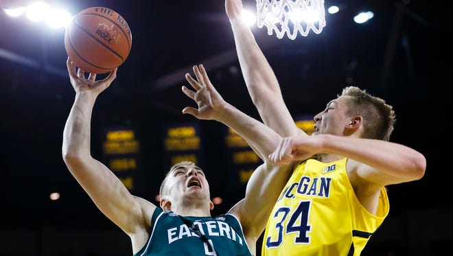 Howell grad Brandon Nazione (4) shoots the ball as Michigan forward Mark Donnal (34) defends in the second half of Tuesday's game. Eastern Michigan won 45-42 and will meet Michigan State on Dec. 17 at East Lansing.