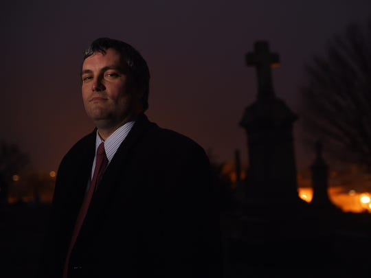 Brett Talley poses for a portrait at Holy Rood Cemetery