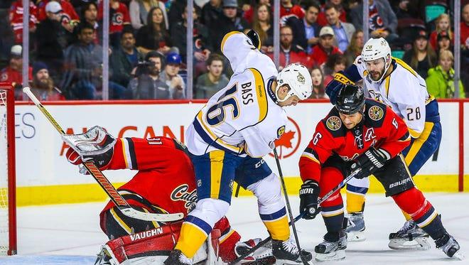 Calgary Flames goalie Karri Ramo (31) guards his net as Nashville Predators center Cody Bass (16) and Calgary Flames defenseman Dennis Wideman (6) battle for the puck during the first period at Scotiabank Saddledome.