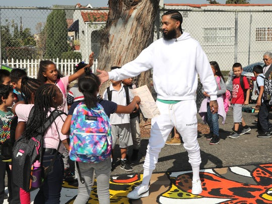 Nipsey Hussle greets children at Nipsey Hussle x PUMA Hoops Basketball Court Update reveals event in October. 22, 2018 in Los Angeles.