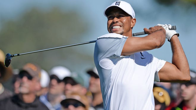 Tiger Woods hits his drive on the 12th during the first round of the Farmers Insurance Open golf tournament at Torrey Pines. Woods, who started his round on the back nine, didn't finish 12 holes before he withdraw as he surgically repaired back tightened up.