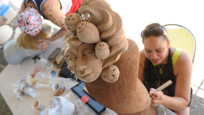 New Zealand artist, Carla Ruka, etches lines resembling flowing water onto a a sculpture depicting Guam's legend of Sirena during a Festival of Pacific Arts visual arts demonstration in sculpting and pottery at the University of Guam's Isla Center of the Arts in Mangilao on Tuesday, May 31.