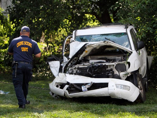 An investigator examines a heavily damaged SUV before it is towed from the scene of a fatal accident in North Philadelphia, Friday July 25, 2014. Two children were killed and three people critically injured when a hijacked car lost control and hit a group of people near a fruit stand, according to police.