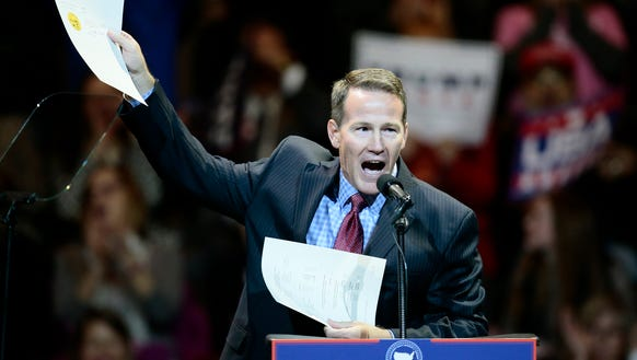 Ohio Secretary of State Jon Husted waves the papers