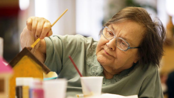 Shirley Chaulklin, one of the members of Bridgewood Nursing & Rehab, paints a birdhouse to help support Helping Paws Pet Pantry.