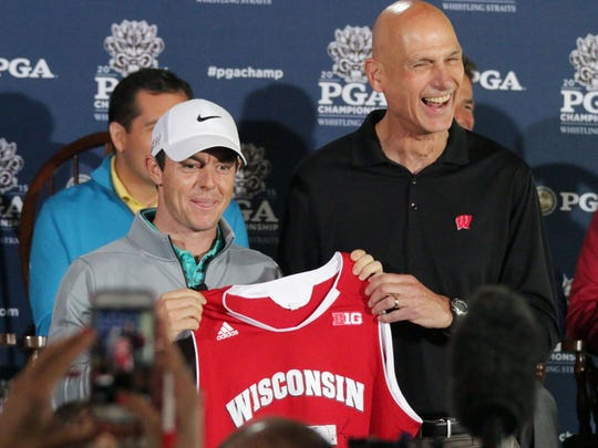 Rory McIlroy, left, smiles as Sam Dekker's dad, Todd Dekker, hands him a Wisconsin Badgers jersey during media day Friday at Whistling Straits.