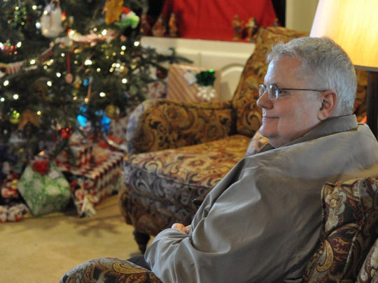 Mark Schneider sits in the living room of his Alexandria home on Sunday. His family's Christmas tree glows in the background and will remain up through Epiphany on Wednesday. For the Schneiders, Dec. 25 marks only the beginning of the Christmas season.