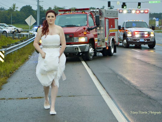 In this Oct. 3, 2015 photo provided by Marcy Martin Photography, her daughter Sarah Ray, in her wedding dress, attends to a car crash in Clarksville, Tenn. Ray's father and grandparents where in a car crash on their way to Ray's wedding reception. Ray, who is a paramedic, went to the scene to check on her relatives. (Marcy Martin Photography via AP)