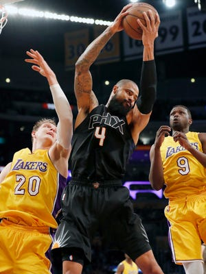Suns center Tyson Chandler, center, comes down with the rebound between Lakers center Timofey Mozgov, left, and forward Luol Deng, right, during the first half, Friday, Dec. 9, 2016, in Los Angeles.