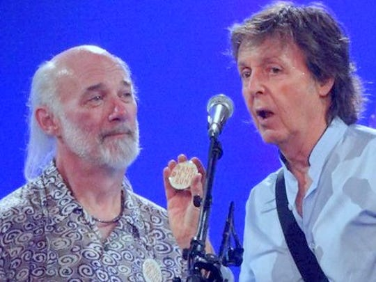 Paul McCartney fan Rick Glover of Atlanta is pulled on stage in Columbia, South Carolina.