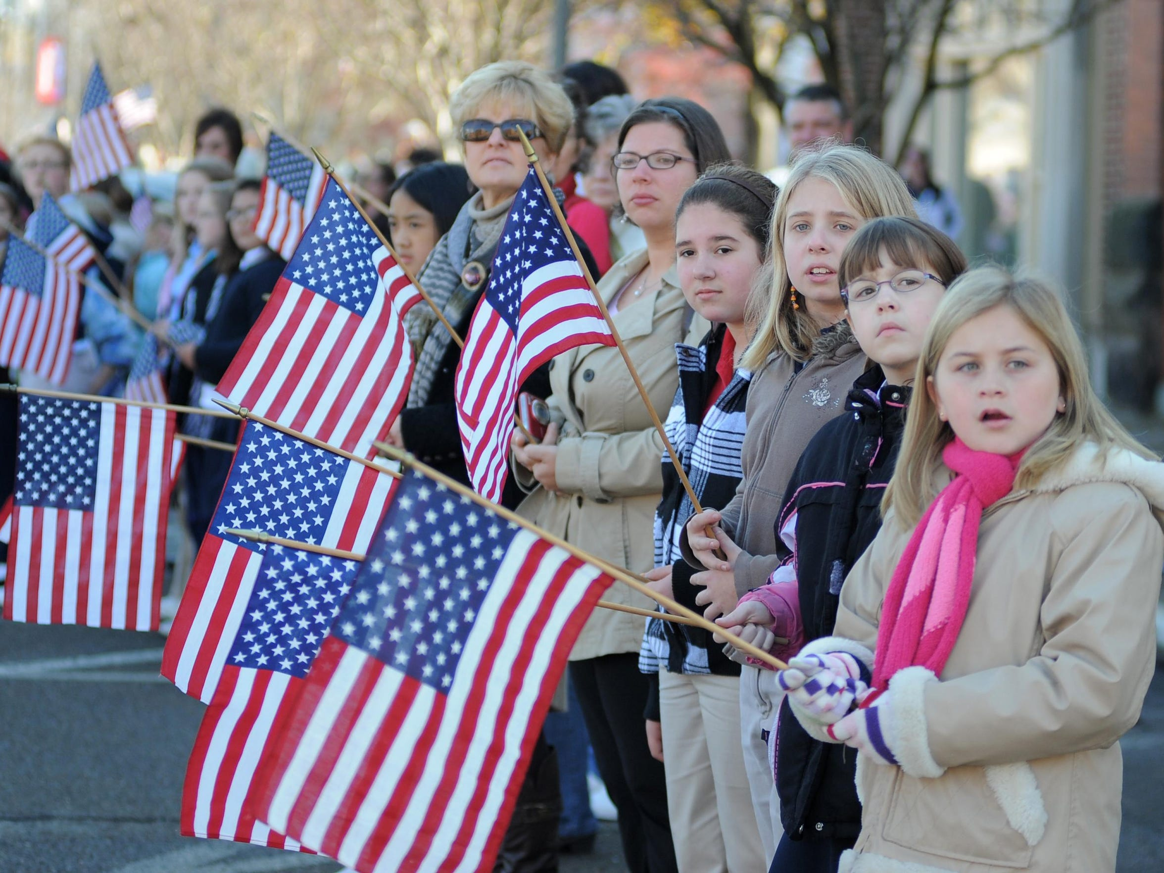 Students from Sacred Heart School stand along Main Street in Coshocton with flags awaiting the arrival of CPO Ray Border's motorcade in this November 2011 file photo.