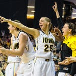 Iowa's Bethany Doolittle (51), Kali Peschel (25) and Kathryn Reynolds (33) cheer after a mad three-pointer against Minnesota during the second half of play on senior day at Carver-Hawkeye Arena in Iowa City on Sunday, March 1, 2015. The Hawkeyes beat the Gophers 92-76.