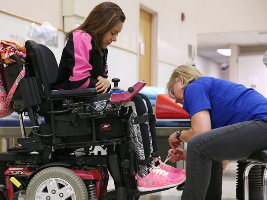 Physical therapist Kim Deckman helps Ben Davis graduating senior Macy Huff into leg braces before a session at Rehabilitation Hospital of Indiana, Indianapolis, Friday, May 20, 2016. Huff attends rehabilitation sessions twice a week, walking increasing distances with Deckman's assistance, leg braces and a walker.