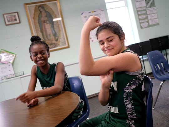 "Most Holy Trinity School JV girls basketball team member Olivia Torres, right, talks about her nickname ""Invisible Muscles"" as teammate Aniah Thomas watches at their school in Detroit on Wednesday."