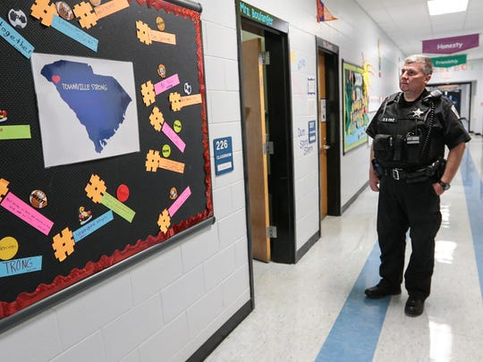 Steven Cole, right, school resource officer at Townville Elementary School, stands near #TownvilleStrong artwork on Thursday at the school in Townville.  Students created a variety of hashtag expressions, displayed in the hallway. Some are #StickTogether, #BeingLoving, #HelpPeople, #BeBrave, and #BeAnAwesomeStudent.