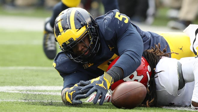 Michigan defensive lineman Aubrey Solomon tackles Rutgers' Janarion Grant, who was ruled down on the play, in the third quarter on Saturday at Michigan Stadium.