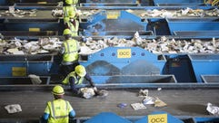 Workers sort out waste materials at a recycling facility