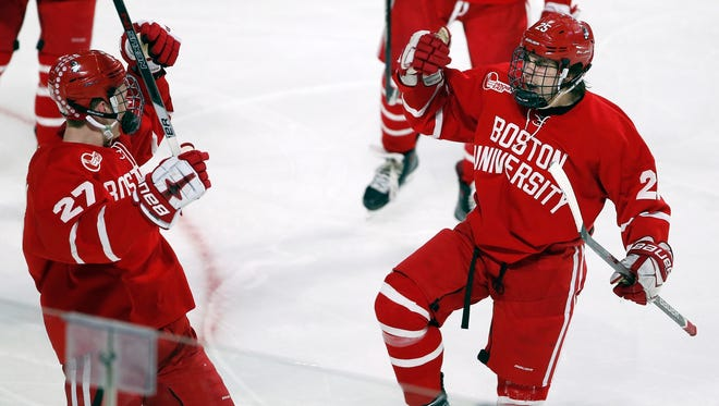 Boston's David Farrance (25) celebrates his goal with teammate Brady Tkachuk (27) during the third period of an NCAA college hockey tournament regional game against Cornell in Worcester, Mass., on March 24, 2018. Boston won 3-1.