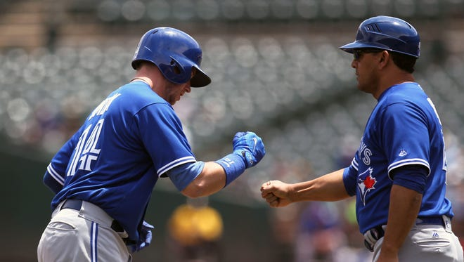 The Blue Jays' Justin Smoak, left, celebrates his solo home run with third-base coach Luis Rivera, right, in the second inning off their game against the Athletics at Oakland Coliseum.