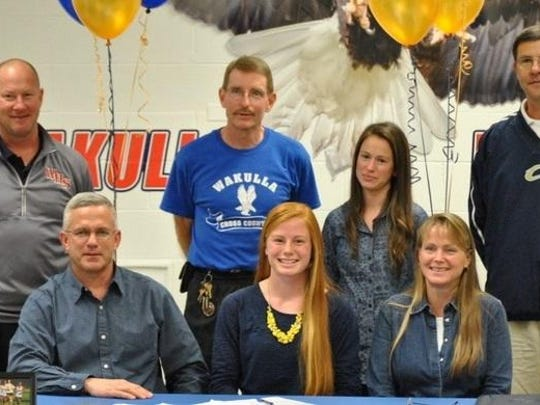 Wakulla coach Paul Hoover stands with runner Margaret Wiedeman and her family in 2014 when she signed to run for Chipola College's cross country team.