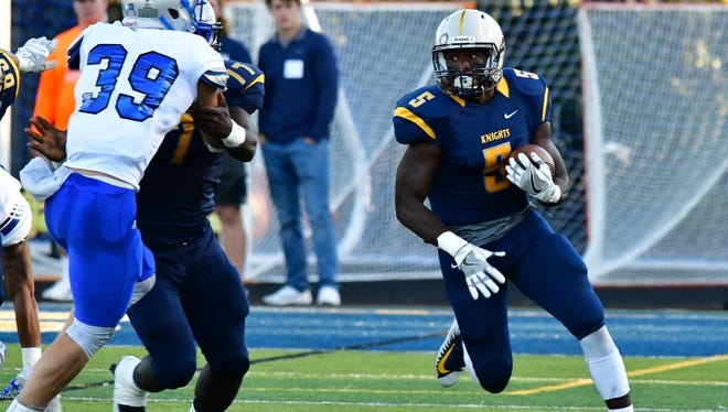 Marian's Maurice Woodard (5) looks for running room against St. Francis on Saturday.