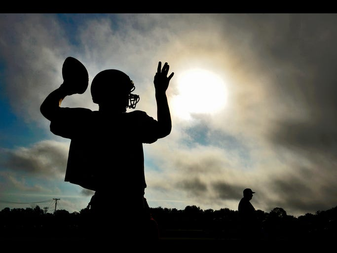 Apollo High School quarterback Ben Alvord warms up to start practice as the sun peeks through the clouds Wednesday morning, Aug. 20.